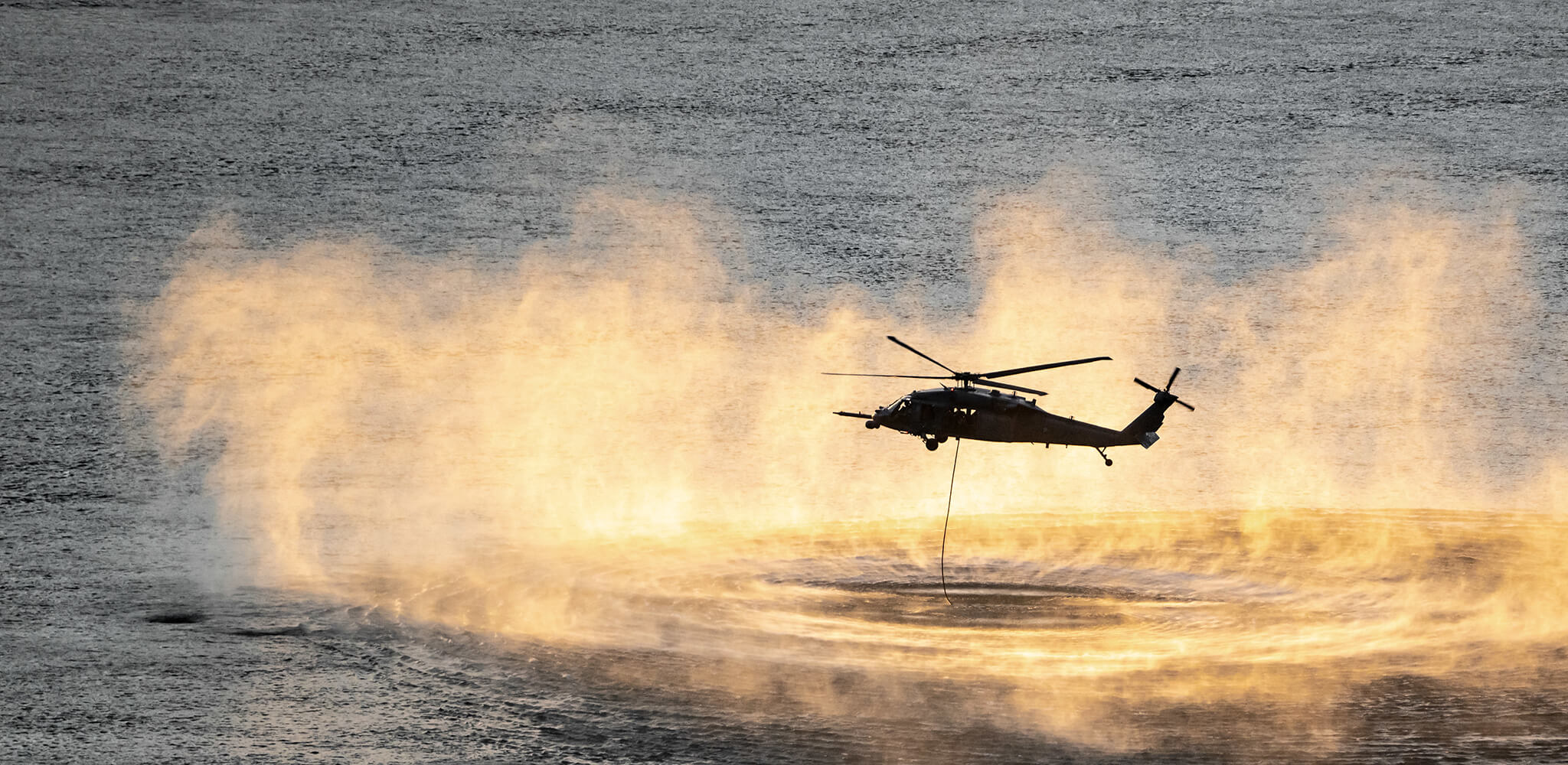 Up close shot of helicopter performing training rescue operation over the columbia river at sunset
