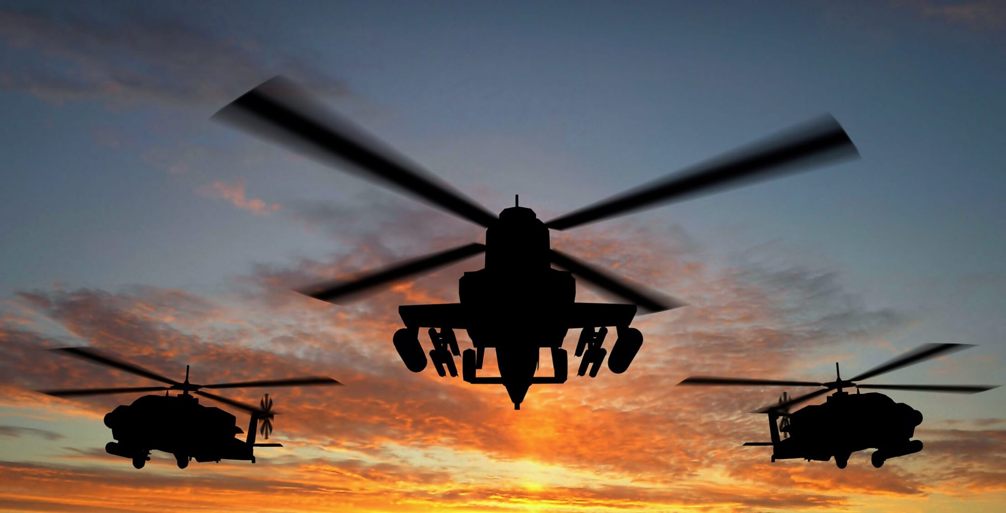Silhouette of helicopter over sunset
